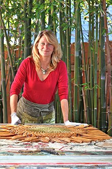 Artist Betsy Schulz cleans handmade sculpted tiles
